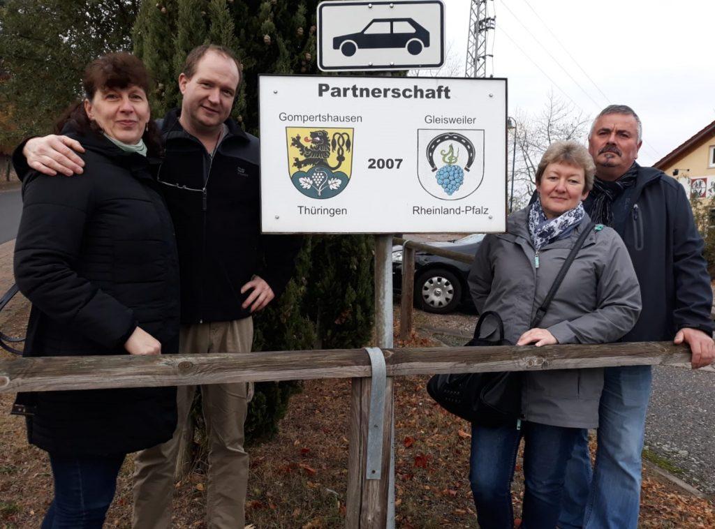 Botschafter aus Gompertshausen vor dem Schild der Ortspartnerschaft.