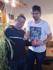 Thomas Böhm überreicht dem Letztplatzierten Christoph Marquis das obligatorische Kartenspiel zum Üben