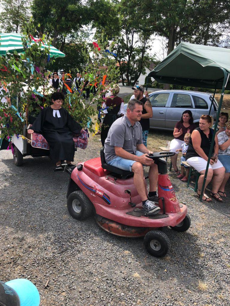 Die Kirmespfarrerin wird per Rasenmäher-Traktor vorgefahren
